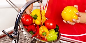 Woman washing fruit at kitchen.